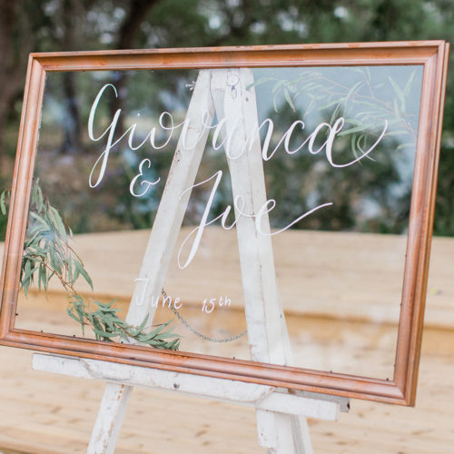Clear Welcome Sign with White Writing And Greenery Details in Copper Frame at Park 31 by CalliRosa