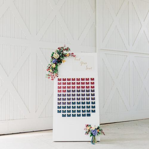Custom Escort Card Wall With Jewel Toned Escort Cards and Gold Acrylic Sign at Hangar 9 by CalliRosa