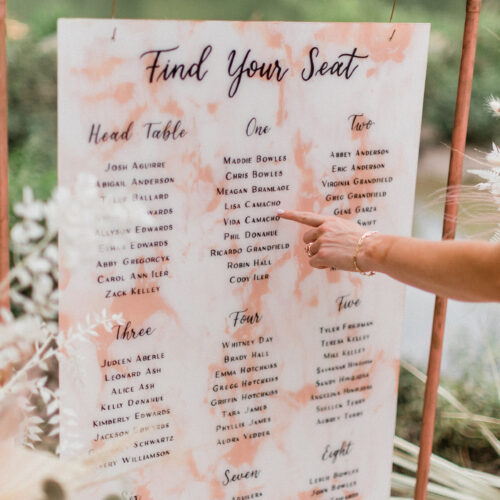 Dusty Rose and White Marbled Seating Chart on Copper Sign Stand with Black Calligraphy at Shiraz Gardens in Austin Texas by CalliRosa