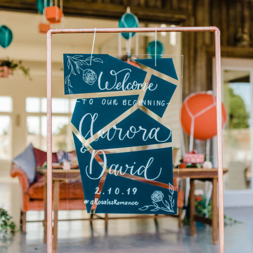 Teal Acrylic Welcome Sign with Geometric Background Pattern on Copper Stand at Sunset Ranch Event Center by CalliRosa